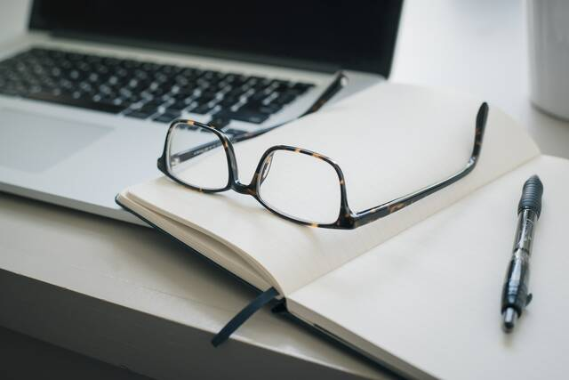 A pair of glasses and a pen on an open notebook next to a laptop - Brille-2 - Ihr Augenoptiker in Hofgeismar